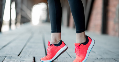 Sports woman in running shoes standing on toes on the wooden floor, close-up view focused on the sneakers